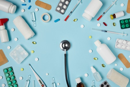 top view of stethoscope surrounded with various medicines on blue surface Stock fotó