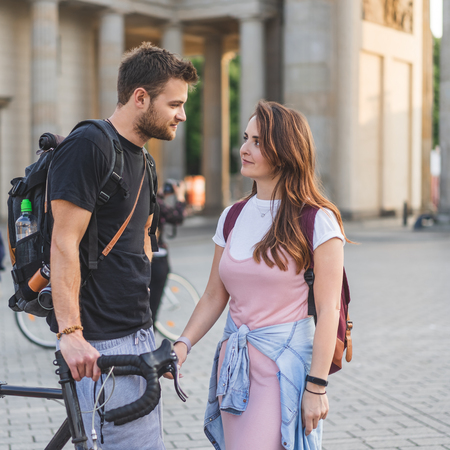 couple of tourists with backpacks looking at each other at Pariser Platz, Berlin, Germany Stock Photo