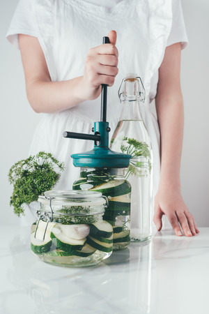 cropped image of woman preparing preserved zucchini at kitchen Banco de Imagens