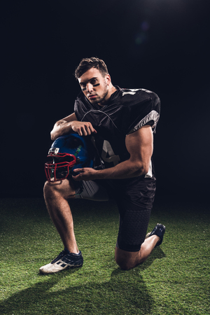 handsome american football player standing on one knee on grass with helmet on black Archivio Fotografico - 105582343