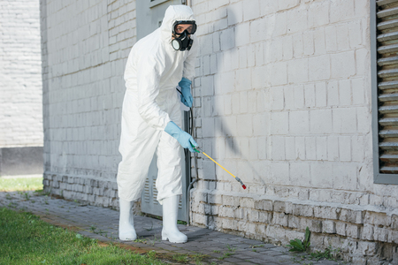pest control worker spraying chemicals with sprayer on building wall Reklamní fotografie
