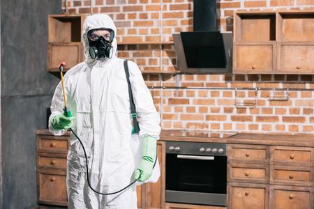 pest control worker standing with sprayer in kitchen