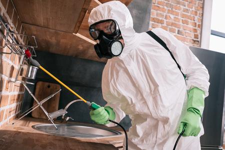 Trabajador de control de plagas rociar pesticidas en estantes metálicos en la cocina