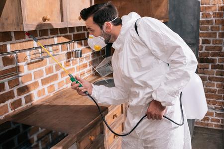 Vista lateral del trabajador de control de plagas rociando pesticidas bajo los estantes de la cocina