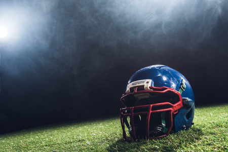 close-up shot of american football helmet on green grass with white smoke above Standard-Bild - 105582525