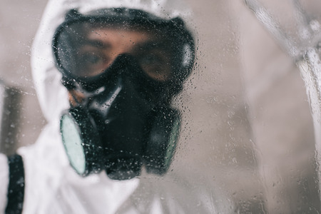 pest control worker standing in respirator in bathroom and looking at camera