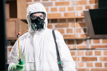 pest control worker standing with sprayer in kitchen and looking away Stock Photo