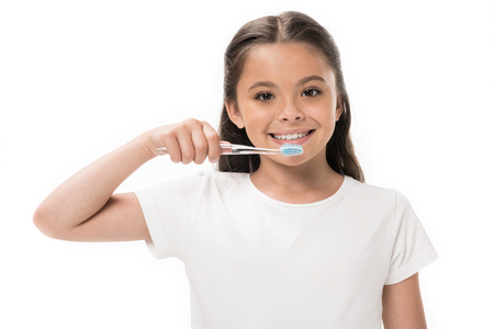 portrait of smiling kid with toothbrush looking at camera isolated on white