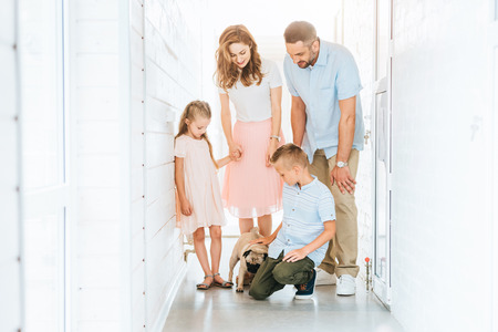 parents and children looking at adopted pug dog in corridor of animals shelter
