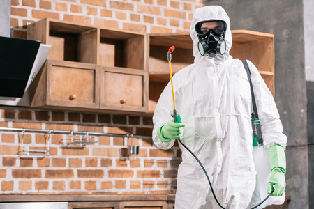 pest control worker in uniform standing with sprayer in kitchen Stock Photo