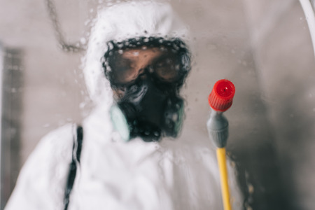 pest control worker standing in respirator in bathroom with sprayer