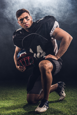 attractive young american football player with helmet standing on knee on black Archivio Fotografico - 105583745