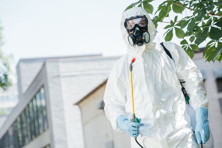 low angle view of pest control worker standing with sprayer