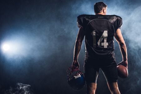 rear view of equipped american football player with helmet and ball in hands against white smoke Reklamní fotografie