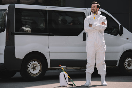 smiling pest control worker in uniform standing with crossed arms near car and sprayer on street Archivio Fotografico