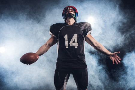 american football player with ball looking up against white smoke Stock fotó