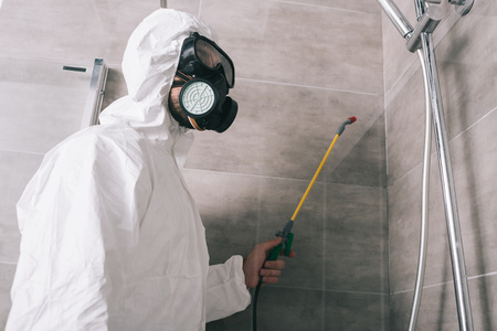 pest control worker in respirator spraying pesticides with sprayer in bathroom Stock fotó