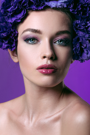 close-up portrait of beautiful young woman with eustoma flowers wreath on head looking at camera isolated on purple Stock Photo