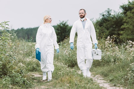 female and male scientists in protective suits walking with working suitcase and clipboard in meadow Stock Photo