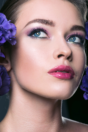close-up portrait of beautiful young woman with fashionable makeup and eustoma flowers Stock Photo