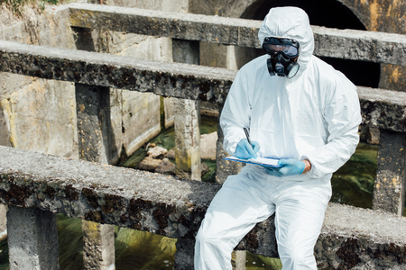 male scientist in protective mask and suit writing in clipboard while sitting near sewerage