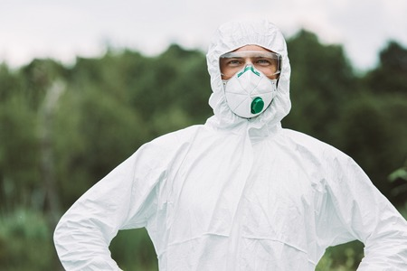 selective focus of smiling male scientist in protective mask and suit looking at camera outdoors