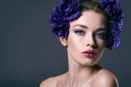 close-up portrait of beautiful young woman with eustoma flowers on head looking at camera isolated on grey Banco de Imagens