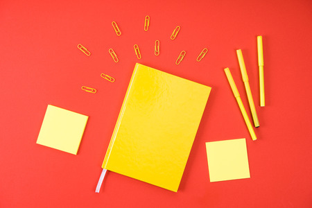 flat lay with yellow notebook with supplies on red