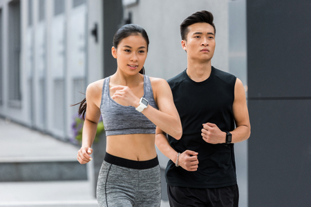 asian sportsman and sportswoman running at city street
