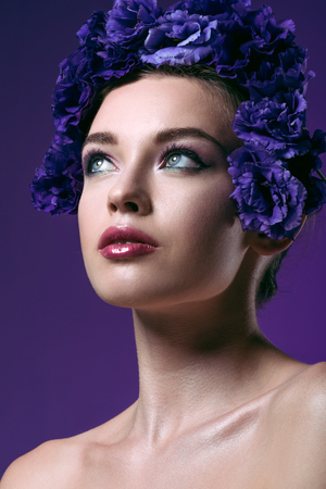 close-up portrait of attractive young woman with eustoma flowers wreath on head looking away isolated on purple