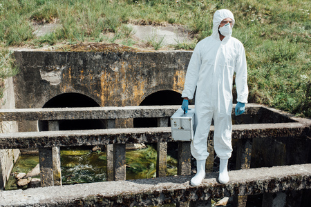 male scientist in protective mask and suit holding working suitcase near sewerage Reklamní fotografie