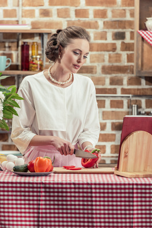 stylish adult housewife in vintage clothes cutting tomato at kitchen