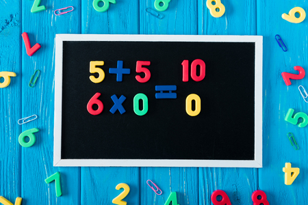 top view of blackboard with math sums, colorful numbers and paper clips on blue wooden background