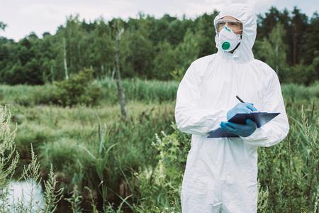El enfoque selectivo del científico masculino en máscara protectora y traje escribiendo en el portapapeles cerca del agua al aire libre