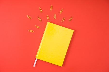 top view of yellow notebook with paper clips on red