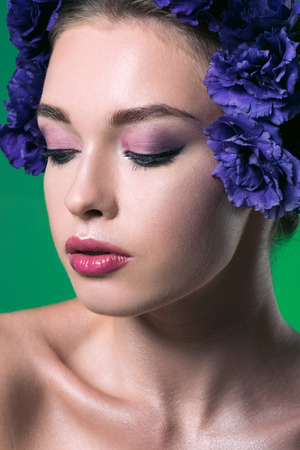 close-up portrait of beautiful young woman with eustoma flowers on head and closed eyes isolated on green
