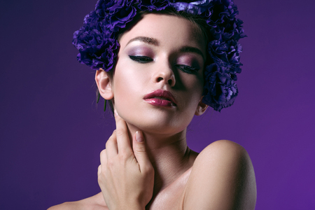 close-up portrait of tender young woman with eustoma flowers wreath on head looking at camera isolated on purple