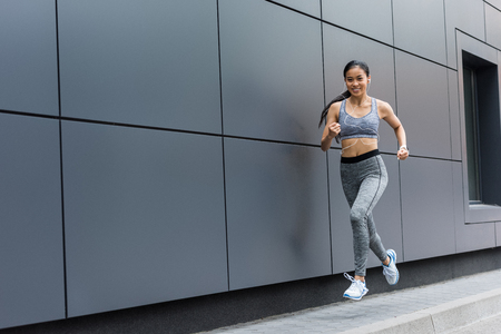 smiling young asian female athlete in earphones running at city street