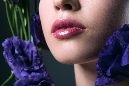 partial portrait of beautiful young woman with pink lips and purple eustoma flowers on grey