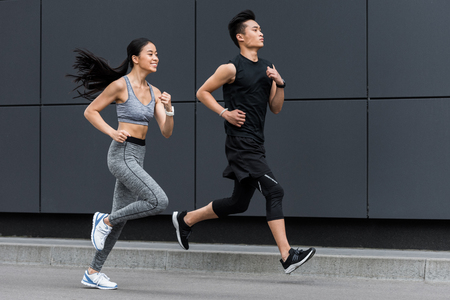 side view of asian sportsman and sportswoman running at city street