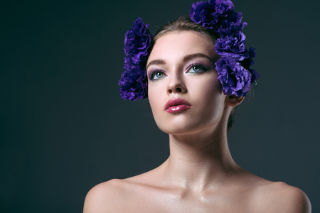 close-up portrait of beautiful young woman with eustoma flowers on head looking away isolated on grey