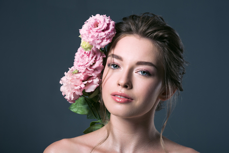 close-up portrait of attractive young woman with pink eustoma flowers behind ear looking at camera isolated on grey