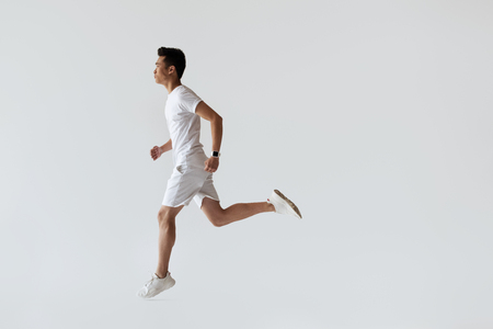 side view of young asian jogger running on grey background Foto de archivo