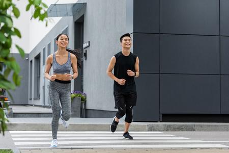 街の通りで走っている笑顔のアジアのスポーツマンとスポーツウーマン 写真素材
