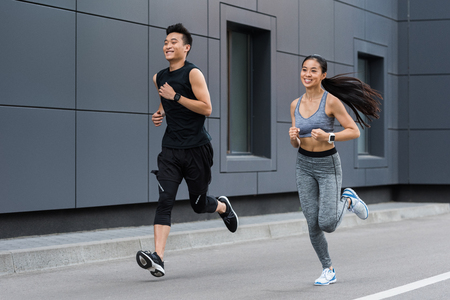 smiling asian female and male athletes running at urban street
