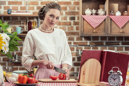 attractive adult housewife in vintage clothes cutting tomato and looking at camera at kitchen