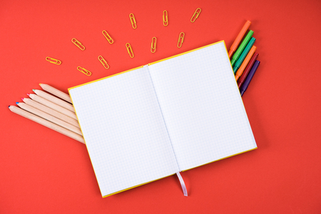 flat lay with opened blank notebook with paper clips, color pencils and markers on red