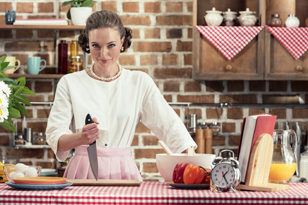 dangerous adult housewife with knife looking at camera at kitchen Stock Photo