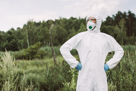 confident male scientist in protective mask, googles and suit standing with hands on waist in meadow