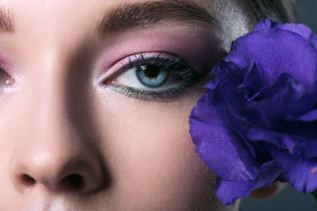 partial portrait of beautiful young woman with pink eyeshadows and purple eustoma flower